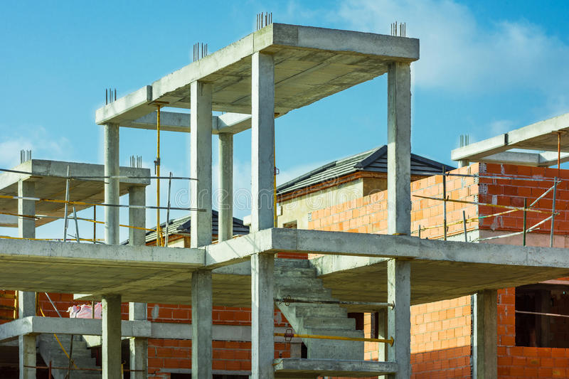 Construction site residential housing development, red brick wall, reinforced concrete pillars, staircase, unfinished in progress. Mediterranean, blue sky royalty free stock image