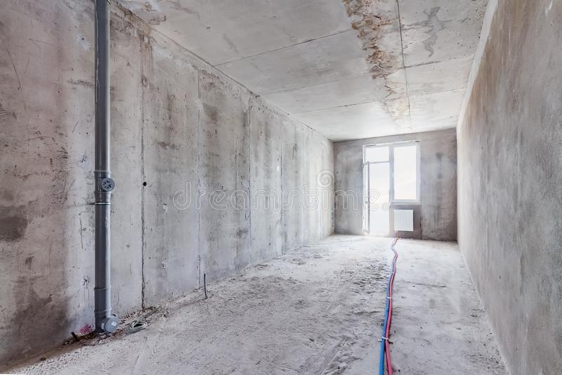 Construction site of residential unfinished apartment building concrete interior in progress with windows and grey trash royalty free stock photography