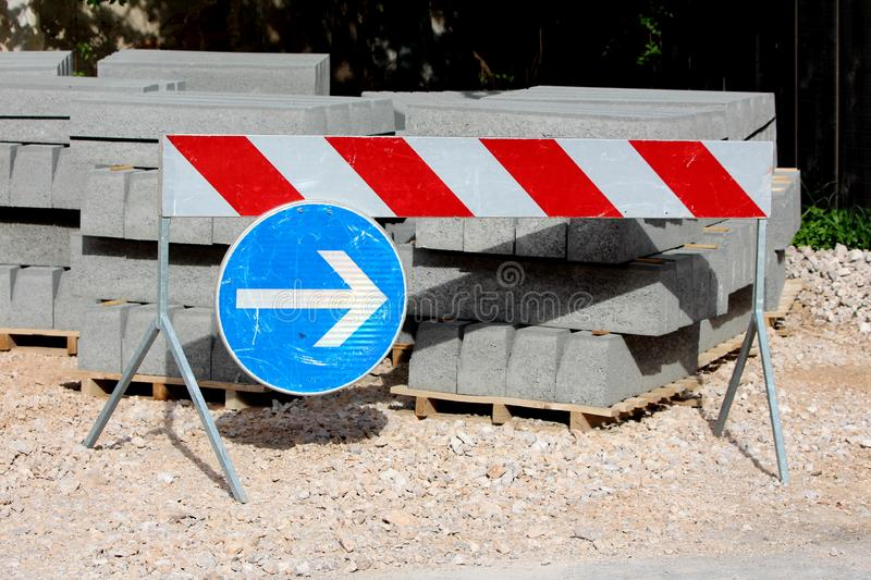 Construction site road signs directing traffic away from concrete curbs building material left on wooden pallets and gravel next. To local road on warm sunny stock image