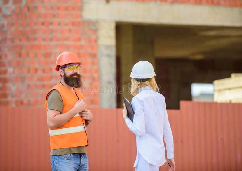 Construction site safety inspection. Discuss progress project. Woman inspector and bearded brutal builder discuss royalty free stock photo