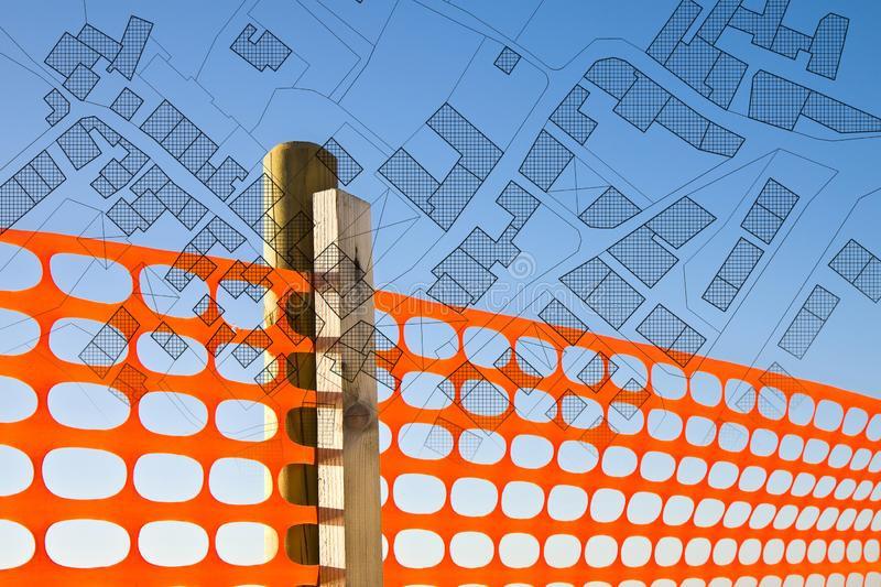Construction site with safety orange grid against a cadastral map - concept image.  royalty free stock image