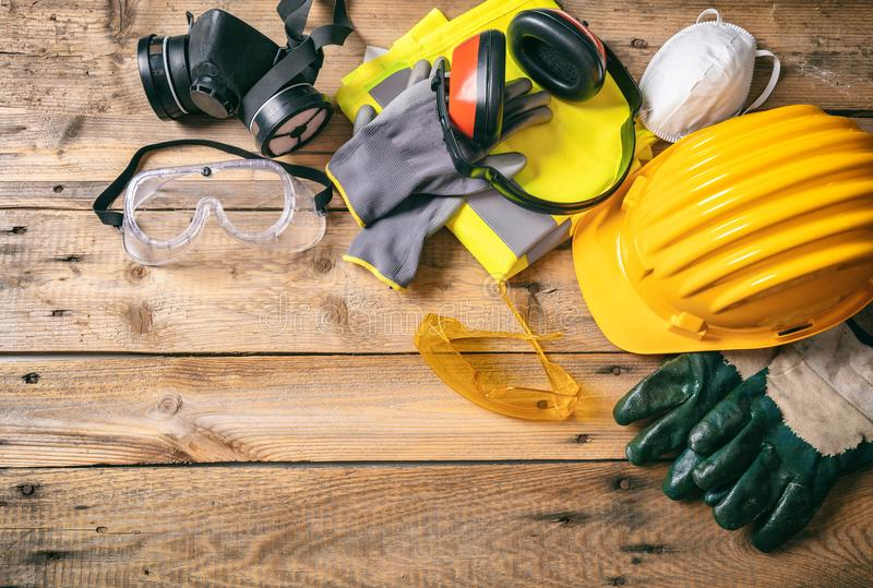 Construction safety. Protective hard hat, headphones, gloves and glasses on wooden background, copy space, top view royalty free stock images