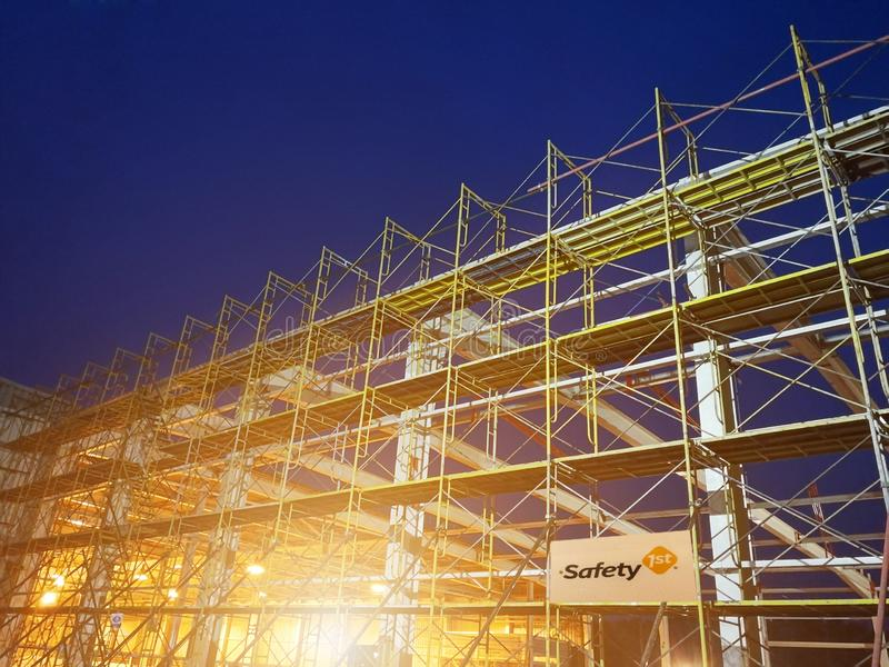 Construction site with scaffold tower and warning label building with dusk background,scaffolding for construction factory royalty free stock image