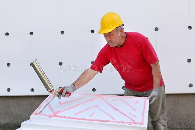 Construction site, styrofoam insulation. Worker applying polyurethane expanding foam glue with gun applicator stock images
