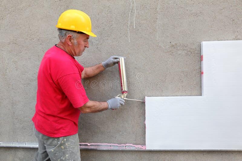 Construction site, styrofoam insulation. Worker applying polyurethane expanding foam glue with gun applicator royalty free stock photography