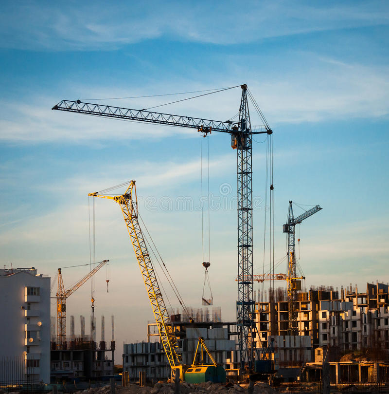 Construction site. At sunset with building cranes. Industrial landscape with cranes on the cloudy sky stock image