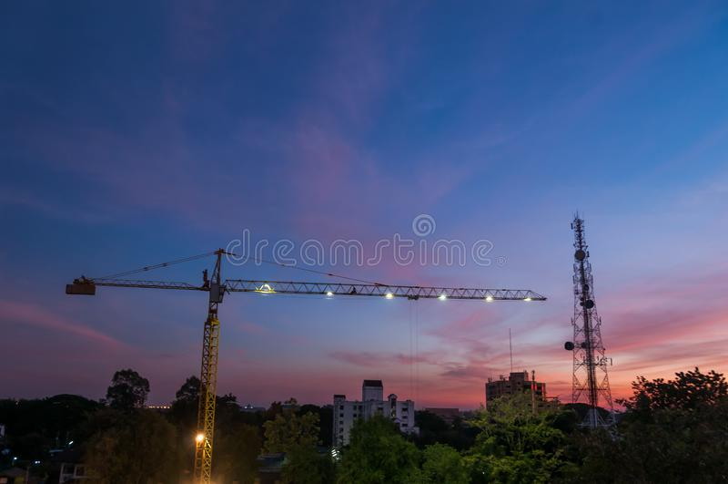 Construction site at sunset. Hoisting cranes and construction site on sunset royalty free stock photo