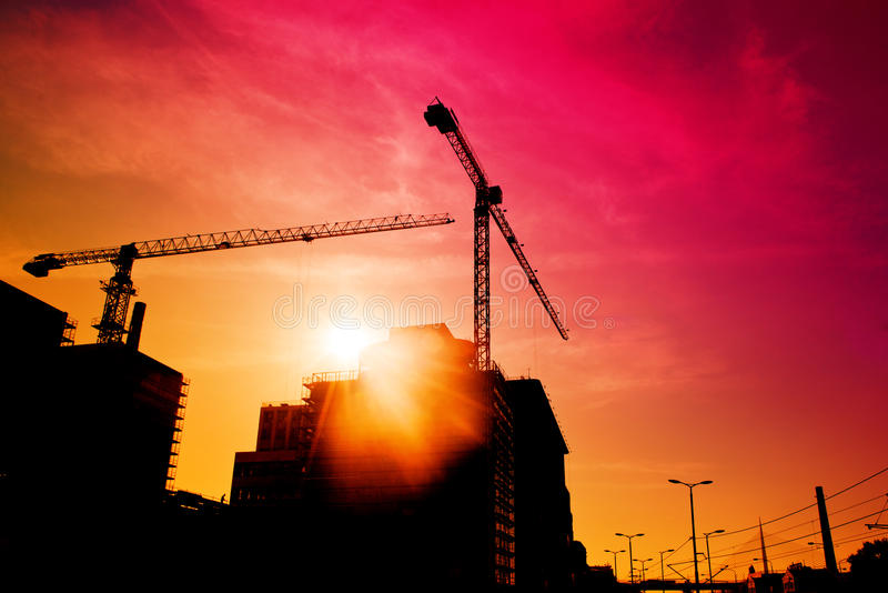 Construction site in sunset. Silhouettes of construction carnes against sun light royalty free stock photo