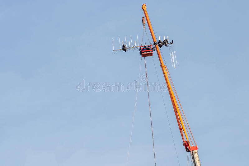 The construction site of telecommunication tower with lifting cr. Ane is working in blue sky sunny day royalty free stock images