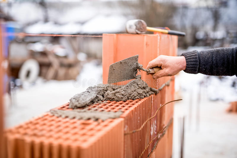 Construction site with worker building brick walls with mortar and bricks. House construction site with worker building brick walls with mortar and bricks royalty free stock images