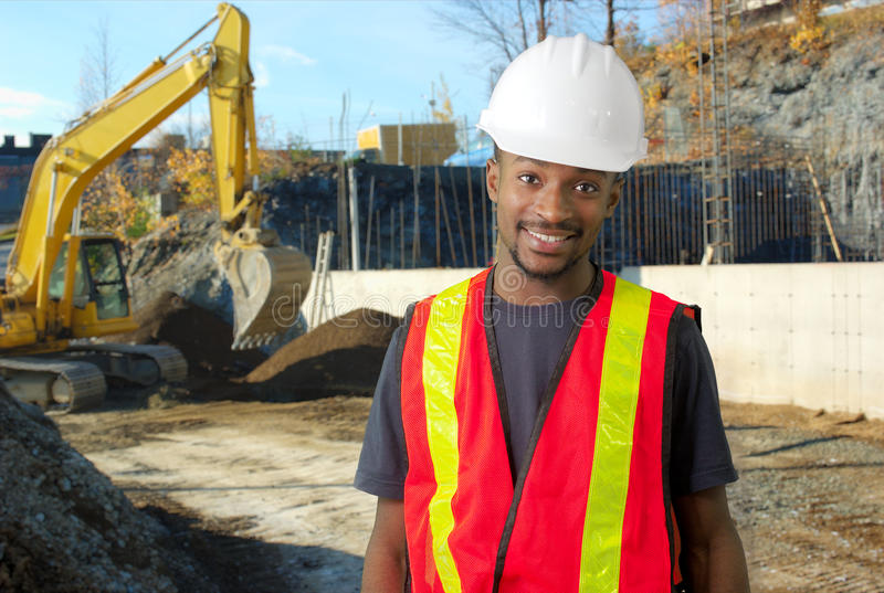 Construction site worker orange jacket and white security helmet royalty free stock photography