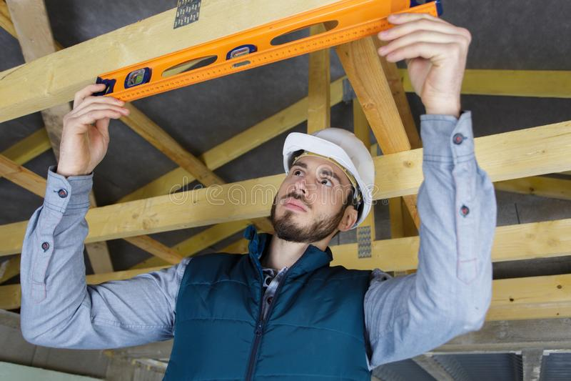 Construction site worker with spirit level checking beam royalty free stock photography