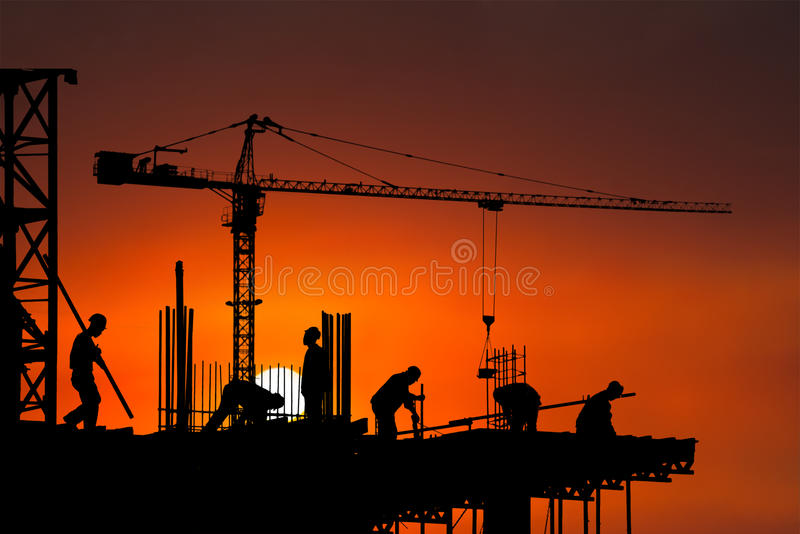 Construction Site, Worker, Workers, Background. Background of construction workers with a sunrise or sunset. Each worker is doing his job at the work site stock image