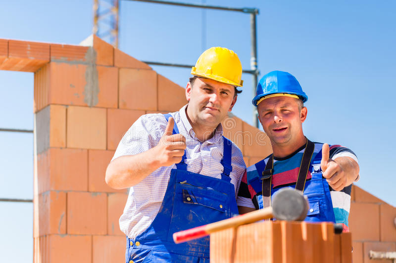 Construction Site Workers Building Walls On House Stock Images
