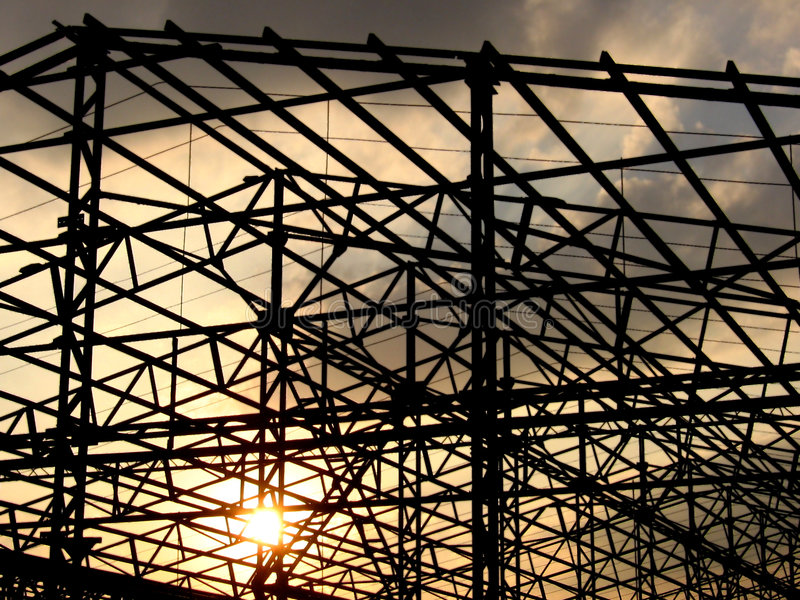 Construction Sunset. The sun sets behind the construction site of a factory royalty free stock photography