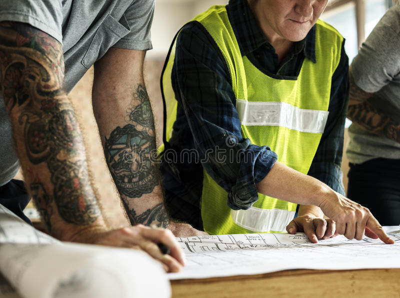 Construction team and blueprint on site royalty free stock images
