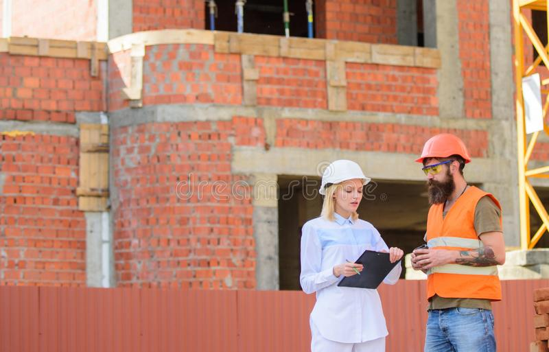 Construction team communication concept. Discuss progress plan. Woman engineer and builder communicate construction site royalty free stock image