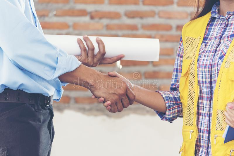 Construction teamwork shaking hands with engineer and foreman in construction site stock image