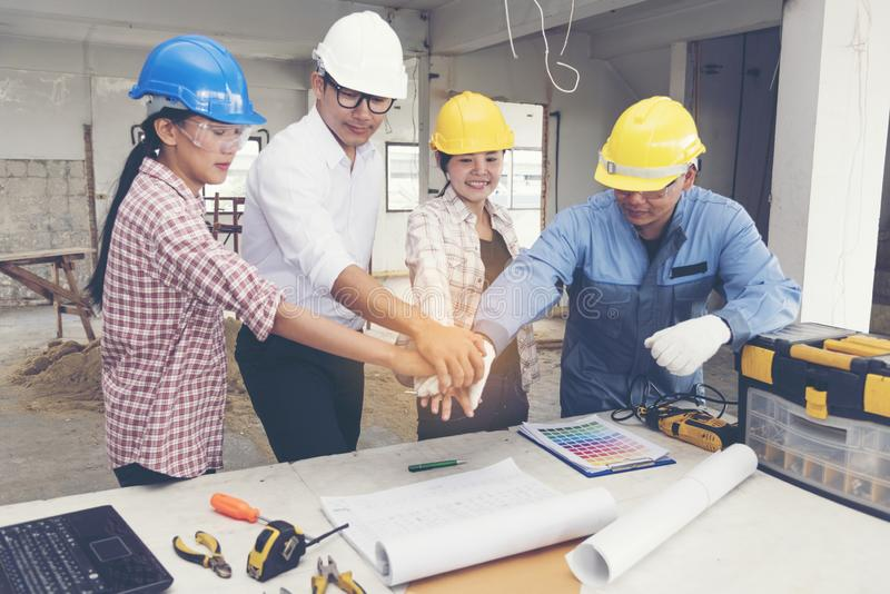 Construction teamwork shaking hands with engineer and foreman in construction site stock photos