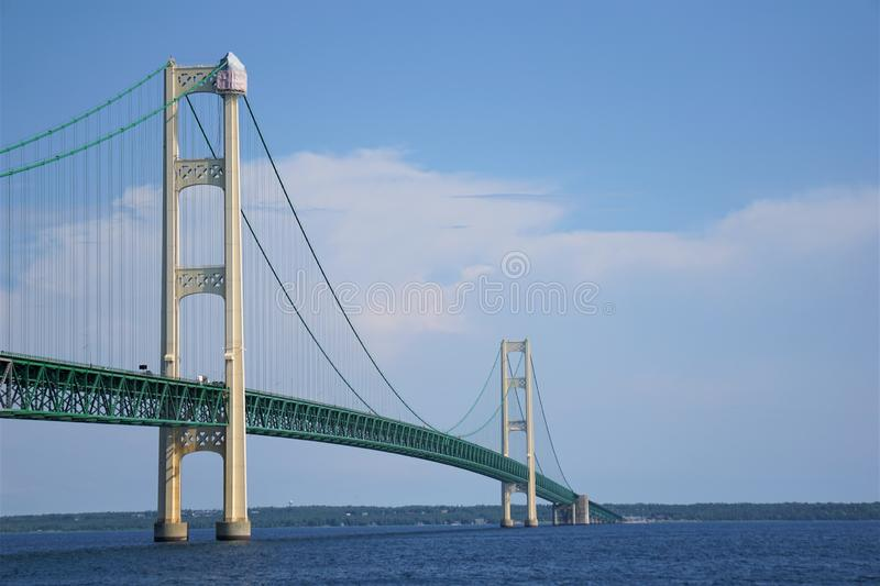 Mackinac Bridge with summer thunderstorm cloud, Michigan, August 2019. Construction tent covers the top of the pier tower of the suspension bridge spanning the stock photos