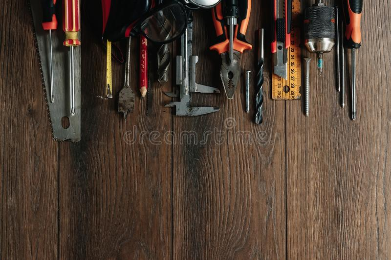 A construction tool on a brown wooden background. View from above. Picture background, screensaver. The concept of construction, stock images