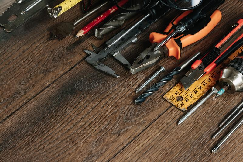 A construction tool on a brown wooden background. View from above. Picture background, screensaver. The concept of construction, stock photography