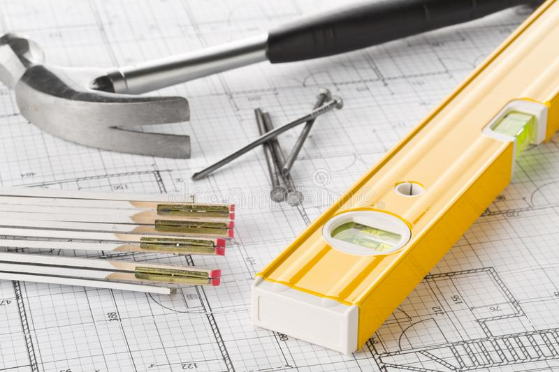 Construction tools with hammer, nails, folding rule and level on architectural blueprint plan royalty free stock photos