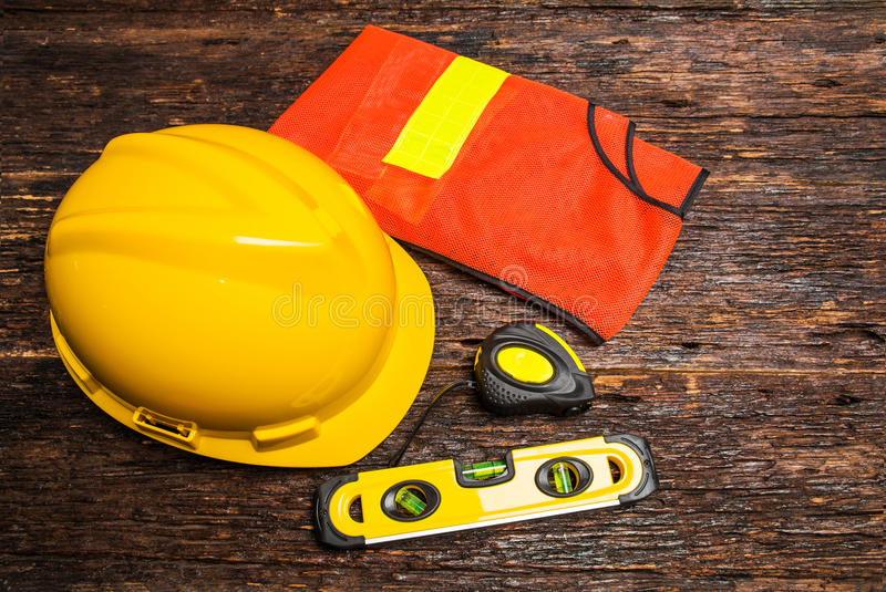 Construction tools or safety equipment with yellow helmet on woo. Den table stock image