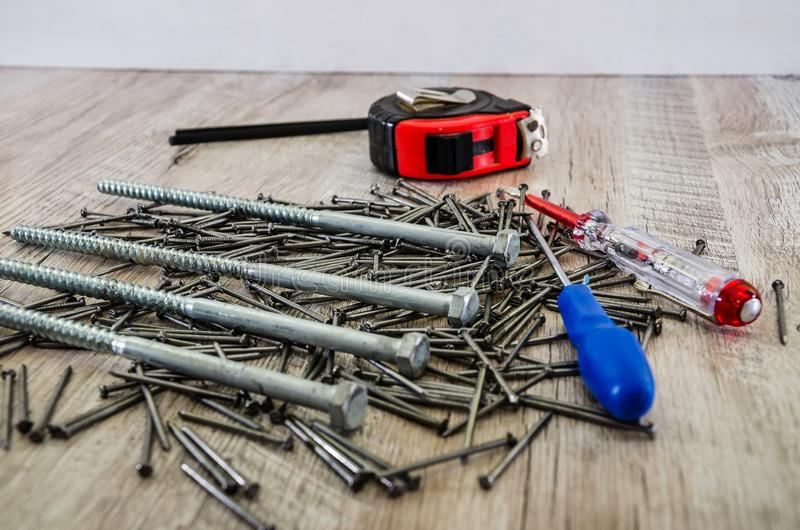 Construction tools on a wooden background. Nails, screws, tape measure, screwdrivers. Construction tools on a wooden background stock photography