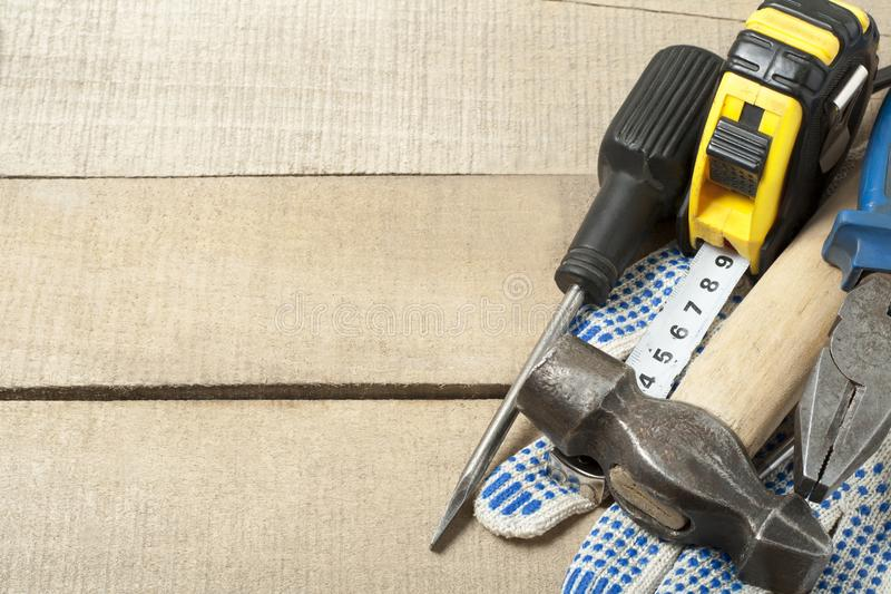 Construction tools and work gloves on wooden background .Copy space for text. stock photos