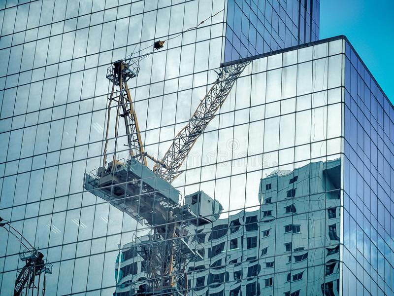 Construction tower cane reflected on the glass office building stock photography