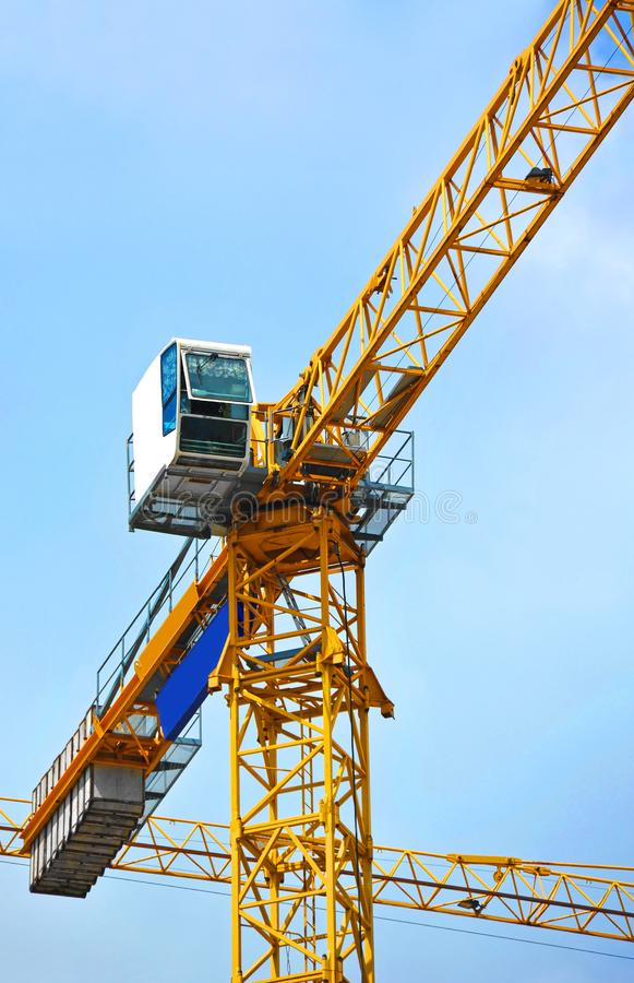 Construction tower crane. Tall construction tower crane against blue sky royalty free stock photography