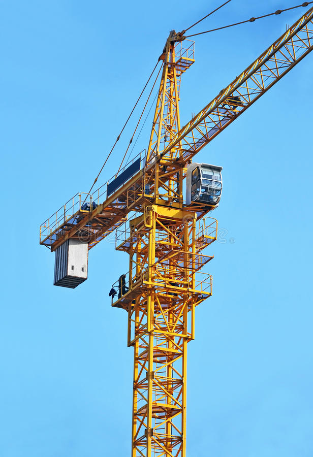 Construction tower crane. Yellow construction tower crane against blue sky royalty free stock photography