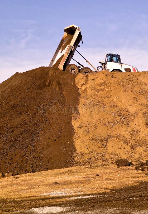 Construction truck tipping dumping raw earth. Soil on site stock image