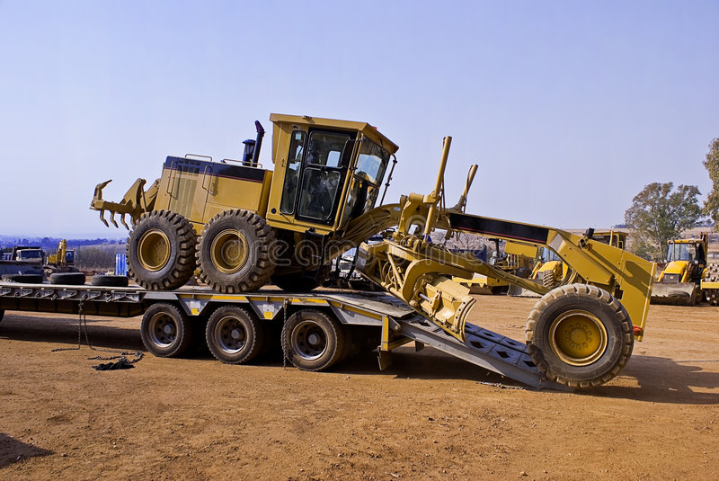 Construction vehicles. Heavy Duty Construction Equipment. Side view of construction vehicle loaded on back of trailer in plant machinery yard royalty free stock photo