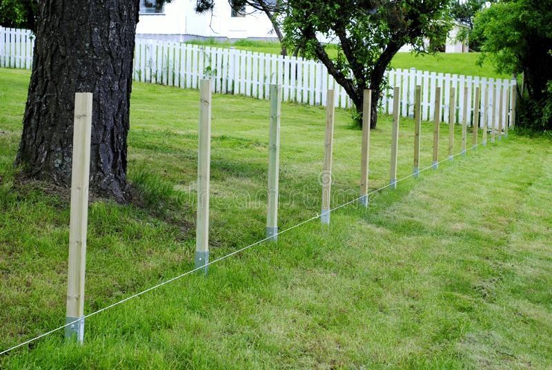Construction of a wooden fence on green grass royalty free stock photos