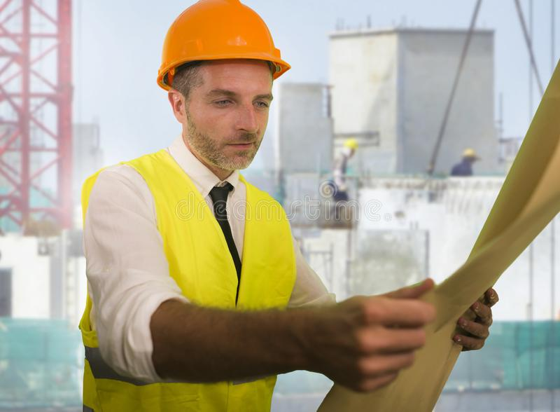 Construction work lifestyle portrait of young happy and attractive engineer or building contractor holding blueprints wearing stock photography