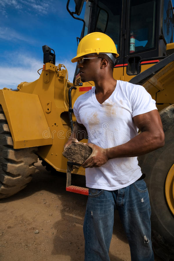 Construction Worker. Handsome young male construction worker wearing a hard hat, white t-shirt and jeans working beside his tractor rig royalty free stock photography