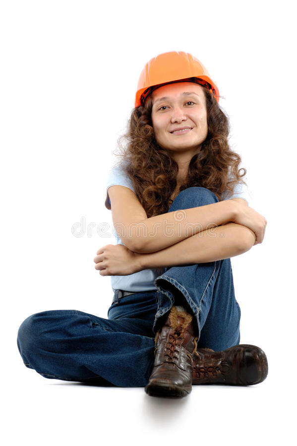Construction Worker. Pretty young woman in a hard hat sitting on white background. Construction worker or intern concept royalty free stock image