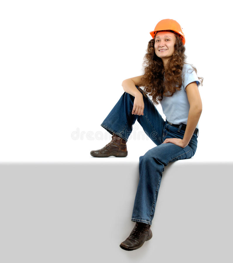 Construction Worker. Pretty young woman in a hard hat sitting on white background. Construction worker or intern concept royalty free stock photography