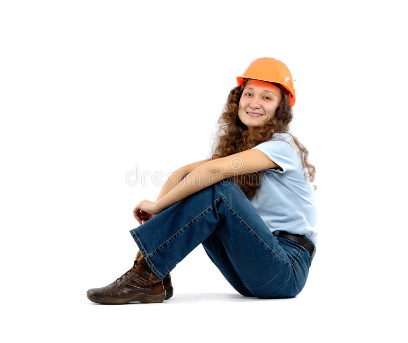 Construction Worker. Pretty young woman in a hard hat sitting isolated on white background. Construction worker or intern concept royalty free stock photos