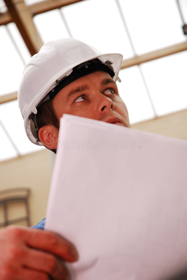Construction Worker. A construction worker looking at plans royalty free stock photos