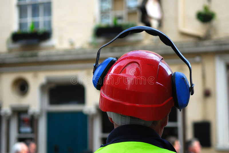 Construction worker. Construction worker wearing safety helmet and ear defenders stock image