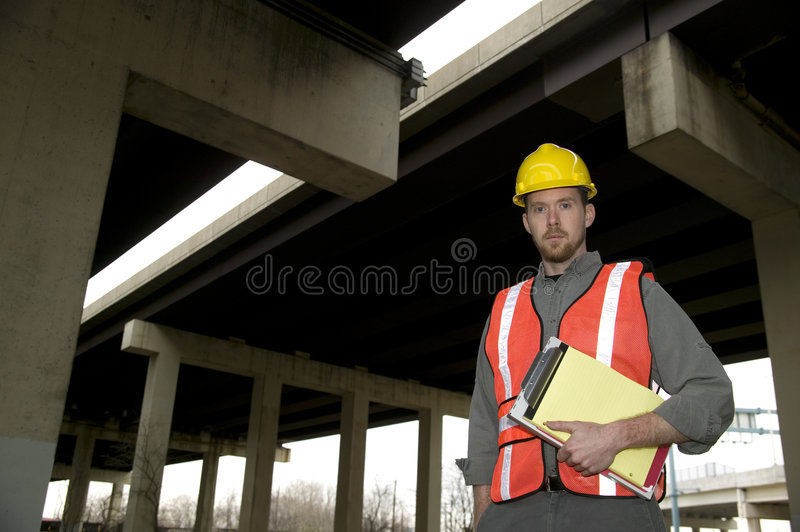 Construction Worker. Stern construction worker wearing a hardhat and carrying a clipboard stock photography