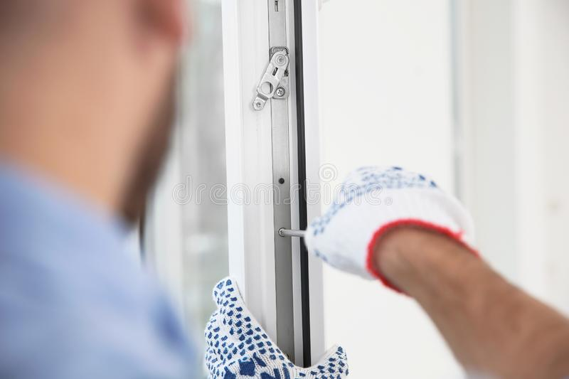 Construction worker adjusting installed window with screwdriver indoors. Closeup royalty free stock photo