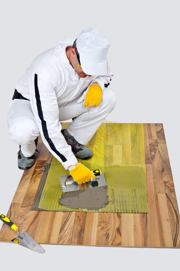 Construction worker applyes tile adhesive on wooden floor royalty free stock photo