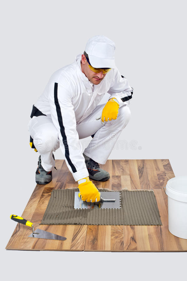Construction worker applyes tile adhesive on wooden floor royalty free stock images
