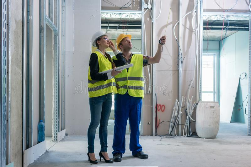 Construction worker and architect discussing work to be done at site royalty free stock photography