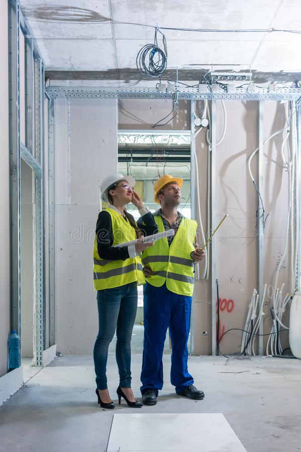 Construction worker and architect discussing work to be done at site stock photo
