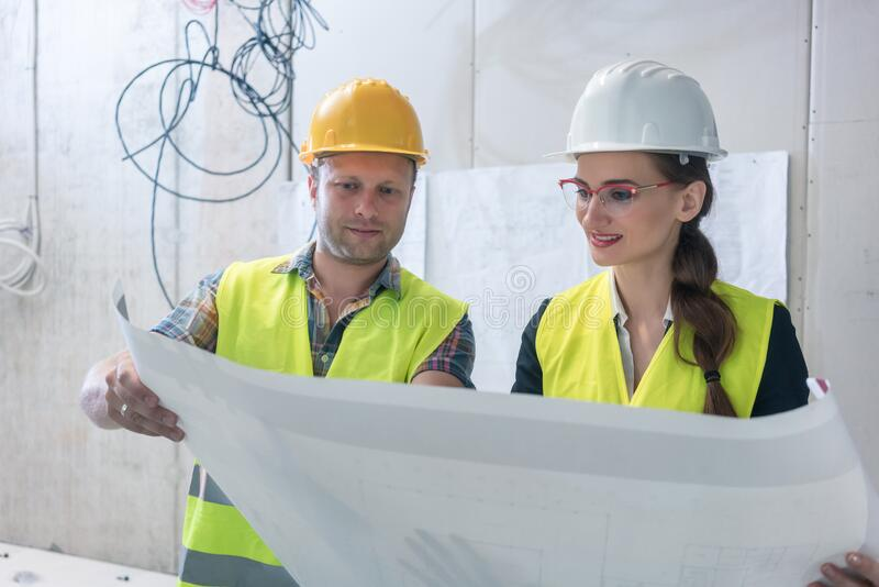 Construction worker and architect reading plan royalty free stock photos